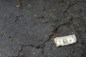 crumpled US Dollar Bill on asphalt street
