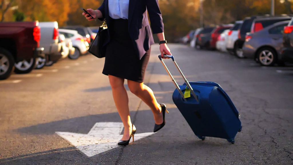Businesswoman pulling suitcase in parking lot at airport while on mobile phone.