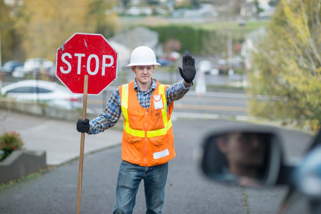Construction worker telling cars to stop