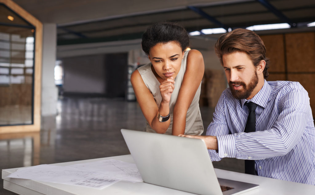 Businessman and woman looking at computer.